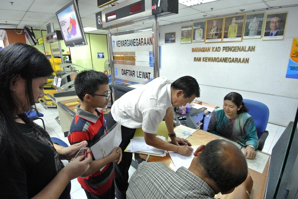 图说人联党公共投诉局主任叶耀星在国民登记局协助来自石角的夫妇办理其小孩的公民权申请。