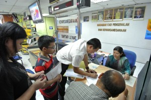 Photo shows SPCB Chief, Wilfred Yap at the National Registration Department assisting the couple from Batu Kawa with their application for citizenship for their child.